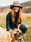 Portrait of smiling woman with dog at countryside field — Stock Photo
