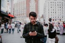 Homme naviguant smartphone sur la rue de la ville — Photo de stock