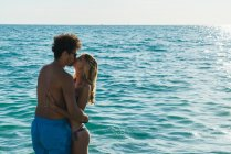 Side view of kissing couple in ocean water — Stock Photo