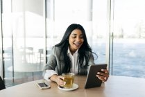 Cheerful stylish businesswoman drinking tea and  looking down at tablet in hand. — Stock Photo