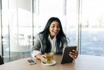 Allegro elegante donna d'affari bere il tè e guardando giù al tablet in mano . — Foto stock