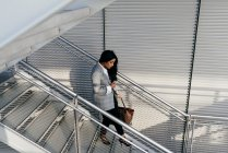 High angle view of elegant businesswoman looking down and carefully walking down stairs — Stock Photo