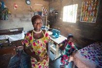 Benin, África - 31 de agosto de 2017: Mulher alegre com filho sorrindo na oficina de pé e olhando para a câmera. — Fotografia de Stock