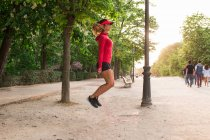 Side view of girl jumping with jump rope at park alley — Stock Photo