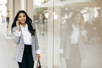 Smiling businesswoman walking along shop windows and talking on phone — Stock Photo