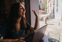 Smiling woman sitting with laptop in cafe looking aside and greeting with gesture — Stock Photo
