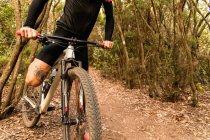 Мужчина с татуировкой на велосипеде на лесной дорожке — стоковое фото