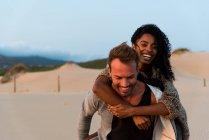 Сміючись, пара постановки на пляж заходу сонця — стокове фото