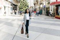 Femme d'affaires élégante marchant dans la rue avec téléphone et sac à main dans les mains et levant les yeux — Photo de stock