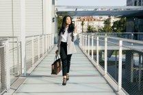 Elegant businesswoman with handbag walking at balcony passage and looking away — Stock Photo