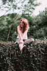 Charming woman sitting on green fence and  smiling at camera. — Stock Photo