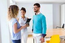 Retrato del grupo de gente de negocios de pie en la oficina moderna y hablando entre sí - foto de stock