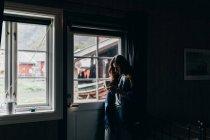 Вид сбоку женщины, стоящей у окна в темной комнате и смотрящей вниз в кружке — стоковое фото