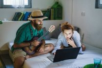 Man in hat with guitar and woman on bed sitting and browsing laptop — Stock Photo