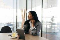 Элегантный бизнес-леди с планшета, сидя за столом и глядя — стоковое фото