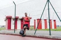 Мужчина в наушниках опирается на забор со смартфоном в руке и смотрит в сторону — стоковое фото