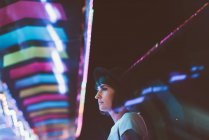 Side view of pensive woman posing in illuminated night park — Stock Photo