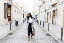 Femme d'affaires souriante marchant avec le téléphone dans la main sur la rue — Photo de stock