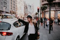 Young woman standing on sidewalk with hand up gesturing to taxi. — Stock Photo