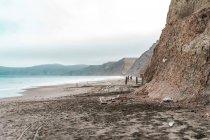 Fernblick von Menschen am Strand, umgeben von Klippen und Felsen. — Stockfoto
