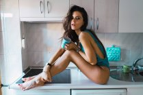 Side view of seductive brunette in body wear posing on kitchen counter with mug and looking at camera. — Stock Photo