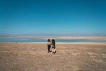 Vista traseira de mulheres andando na areia plana paisagem com lago — Fotografia de Stock