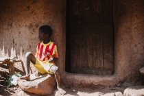 Goree, Senegal- 6 de diciembre de 2017: Niño descalzo sentado en el porche de piedra de la pobre casa de pueblo  . - foto de stock