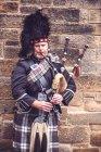 Edimburgo, Escocia - 27 de agosto de 2017: Hombre en traje típico escoc tocando la gaita sobre fondo de pared de ladrillo. - foto de stock