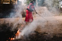 Yoff, Senegal- December 6, 2017: Side view of woman in red wiping straw from street and burning it at street. — Stock Photo