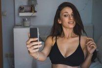 Menina morena no sutiã preto tomando selfie no quarto. — Fotografia de Stock