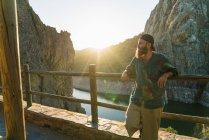 Uomo barbuto che si appoggia sulla rete fissa terrazza sopra il fiume della montagna — Foto stock