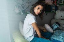 Brunette fille assise sur le lit parmi les coussins et les jouets et regardant la caméra . — Photo de stock