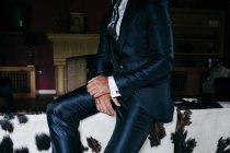 Элегантный мужчина культур в блестящей темно синий костюм, сидя на спине тренер — стоковое фото