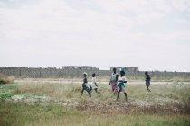 Гори, Сенегал-6 декабря 2017: Группы женщины в традиционной одежде ходить в поле на фоне серых кирпичной стены — стоковое фото