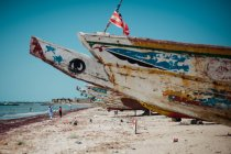 Old rusty boats on sandy shore in cloudless sunny day. — Stock Photo