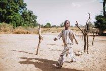 Goree, Senegal- 6 de dezembro de 2017: Menino andando na areia na área rural e olhando para a câmera com confiança . — Fotografia de Stock