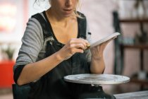 Mid section of female potter carving clay dish — Stock Photo
