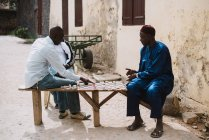 Yoff, Senegal- December 6, 2017: Side view of two African men sitting on street and playing checkers — Stock Photo