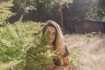 Cheerful girl posing behind fern branches at nature — Stock Photo