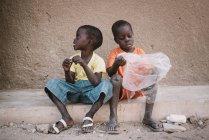 Yoff, Sénégal - 6 décembre 2017: deux petits garçons assis avec un sac en plastique sur le trottoir grungy. — Photo de stock