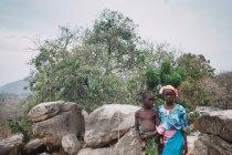 Yoff, Senegal - 6 dicembre 2017: gravi bambini in vestiti luminosi che posa contro le rocce e il paesaggio naturale. — Foto stock
