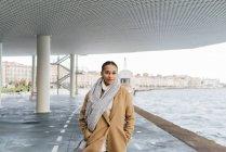 Jovem de casaco andando perto da água — Fotografia de Stock