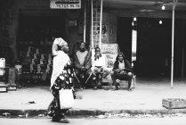Yoff, Senegal- 6 de dezembro de 2017: Vista lateral da mulher com saco de papel andando nas proximidades de três homens sentados no banco na cena da rua — Fotografia de Stock