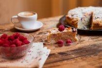 Part du gâteau de framboises aux amandes par tasse de café sur la table en bois — Photo de stock