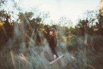 Vue latérale de rousse fille posant avec valise dans le domaine rural et regardant romantiquement loin . — Photo de stock