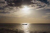 Vue pittoresque de la silhouette du bateau naviguant en mer calme au coucher du soleil . — Photo de stock