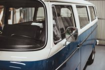 Crop retro blue and white van in garage — Stock Photo