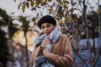 Портрет молодої жінки, які створюють поблизу дерево з гірлянди вогнів — стокове фото