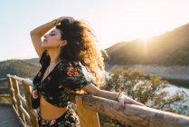 Vista lateral da menina morena, apoiando-se na vedação e agitando o cabelo ao longo da paisagem por do sol — Fotografia de Stock