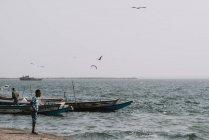 Goree, Сенегалу-6 грудня, 2017:View людей на узбережжі з старого човни, плаваючий на воді і птахів, політ — стокове фото